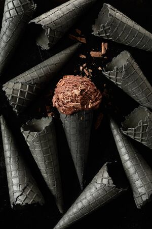 Dark grey monochromatic ice cream cone background with a single scoop of brown chocolate ice-cream covered in flakes in the center cornet
