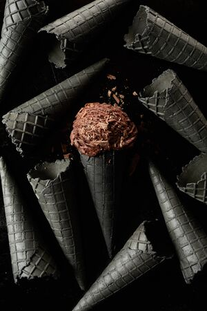 Single scoop of chocolate ice cream covered in flakes amongst many grey colored cones on a black background in a monochromatic image focusing on the dessert