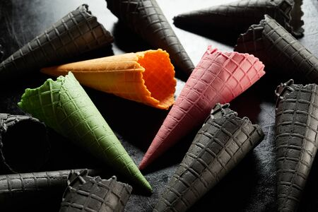 Assorted colors of wafer ice cream cones with single pink, green and yellow ones amongst a selection of black ones over a monochromatic grey background in a close up full frame view