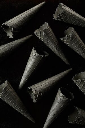 Creative monochromatic grey wafer ice cream cones or cornets scattered on black in a full frame background texture from above