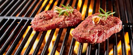 Two portions of raw beef fillet or rump steak seasoned with herbs and spices grilling over a BBQ fire in close up in a panorama banner