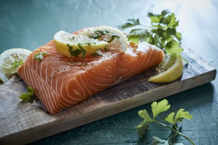 Fresh raw fillet of salmon with herb seasoning and lemon on an old wooden cutting board ready to be grilled