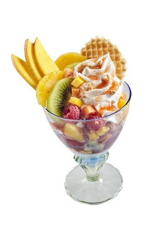 Serving of fresh tropical fruit salad and twirl of ice-cream garnished with sliced apple, kiwi and orange and a wafer biscuit isolated on white 版權商用圖片