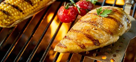 Healthy low fat chicken breast on a BBQ fire grilling over the hot coals with cherry tomatoes and a corncob