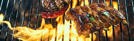 Portion of marinated sticky spicy pork ribs grilling over the flaming coals of a barbecue fire in a wide angle panorama banner with copy space