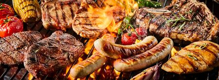Close-up banner with various delicious kinds of pork meat and sausages on barbecue burning grill with fresh tomatoes, corn and spicy herbs