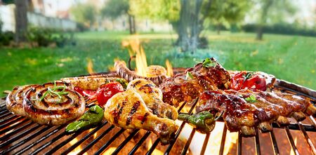 Assorted of mixed meats on a BBQ grilling over the flaming coals in a green spring park or garden with sausage , chicken and spicy pork ribs