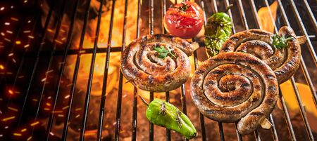 Three spicy sausage coils grilling on a hot BBQ fire with fresh chili peppers and tomato in a close up high angle panorama banner view with copy space
