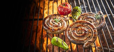 Panorama banner of sausages in neat spirals grilling on a BBQ over the flaming coals with fresh vegetables and copy space