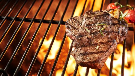 Two portions of thick tender seasoned grilled beef steak on a BBQ grill keeping warm over the hot coals in a panorama banner with copy space