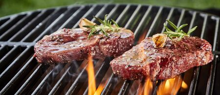 Succulent slices of raw beef steak on a BBQ grilling over the flaming coals in a close up low angle outdoor panorama banner 版權商用圖片