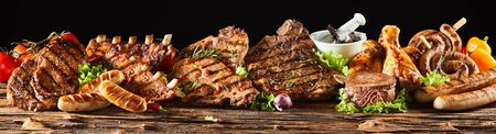 A selection of various barbecued gourmet meats on a rustic timber board with a black background. 版權商用圖片