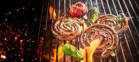 Three coils of spicy beef sausage grilling on a barbecue fire over glowing hot coals in a panorama banner with copy space 版權商用圖片