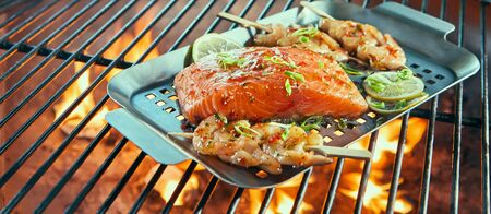 Assorted fresh seafood on a barbecue with prawn or scampi kebabs and a large portion of salmon fillet seasoned with herbs and lemon