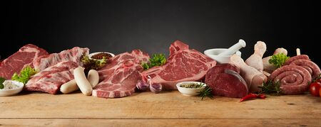 Display of assorted raw meats for barbecuing or grilling with pork, cuts of beef, chicken, sausages, spices and herbs in a wide panorama banner with copy space for advertising