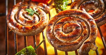 Coils of barbecued sausage on a hot fire grilling over the flames with fresh peppers and tomatoes in a close up view for menu advertising