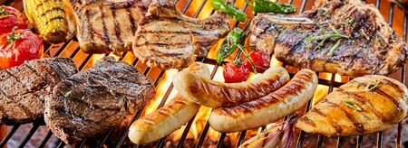 Large assortment of meat grilling on a barbecue over the hot coals with chicken, beef, pork ribs, sausage fresh tomatoes and corn in a panorama banner