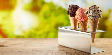 Three flavors of ice cream in cones on an outdoor table standing in a metal holder with blurred garden backdrop of green trees and copy space in panorama banner
