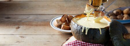 Panorama banner with a delicious traditional Swiss cheese fondue served in a hollwed out pumpkin on a rustic table with accompanying toasted bread and potatoes, with copy space