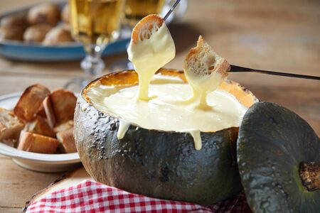 Toasted baguette dipped into melted cheese fondue served in a hollow autumn pumpkin on a rustic table in close up 版權商用圖片
