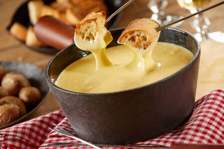 Traditional Swiss cheese fondue in cast iron pot in close up on a rustic table with side dishes showing forks with toasted bread being dipped