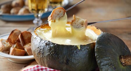 Rustic serving of cheese fondue in a roasted hollow pumpkin rind with toasted baguette for dipping in close up served with white wine