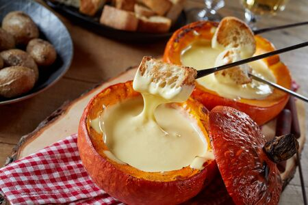 Serving of melted cheese fondue in a restaurant served in a roasted hollowed out pumpkin with toasted baguette and potatoes for dipping and a glass of wine