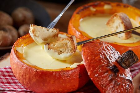 Traditional Swiss fondue with melted raclette cheese served in a hollow roasted pumpkin with toasted baguette for dipping, in close up