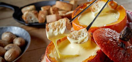 Panorama banner eating a traditional cheese fondue with toasted baguette and baked baby potatoes on forks for dipping in close up