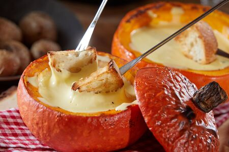 Traditional Swiss cheese fondue in a hollow pumpkin for a delicious hot autumn meal in close up with toasted baguette on dipping forks