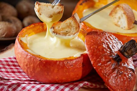 Tasty cheese fondue served in a colorful orange pumpkin rind in autumn in close up with forks dipping toasted baguette