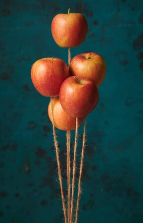 Bunch of ripe red apples floating vertically like balloons on jute threads against blurred blue background