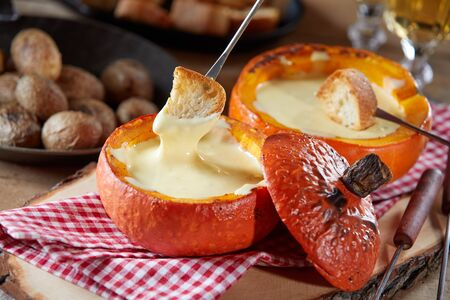 Individual servings of Swiss cheese fondue served with toasted baguette pieces for dipping served in hollowed pumpkin gourds on a rustic table