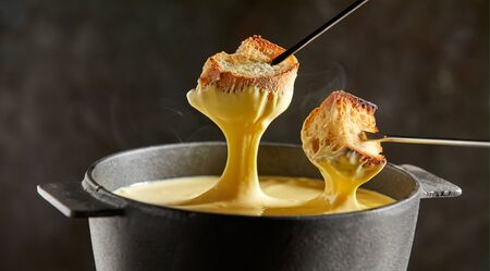 Delicious melted cheese fondue in winter served in a cast iron pot with forks dipping toasted baguette and rising steam over a dark background