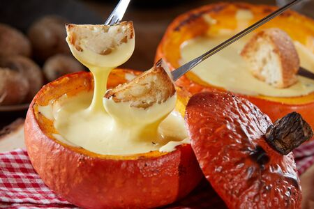 Delicious raclette melted cheese fondue served in a hollowed pumpkin with toasted baguette dipping pieces on forks in close up for a tasty fall meal 版權商用圖片