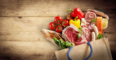 Panorama of assorted meat, fish and fresh produce in a shopping bag spilling out onto a wooden background with vignette and copyspace in a healthy diet concept