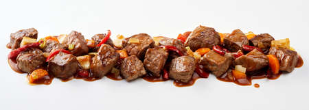 Panorama banner with spicy German goulash with cubed beef or venison, vegetables, chili and a tasty rich gravy isolated on white