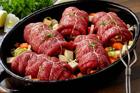 Oven dish with uncooked beef roulades and fresh diced veggies ready for cooking a traditional German meal in a high angle close up