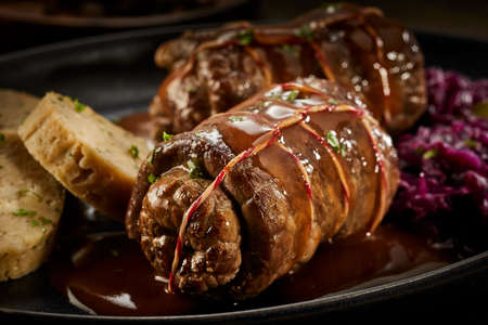 Traditional German beef roulade in a tasty gravy served on a plate in closeup on the meat