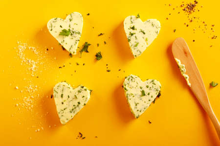 Four decorative heart shaped herbal butter pats with fresh parsley on a tropical yellow background with wooden spatula viewed from overhead in a food styling concept