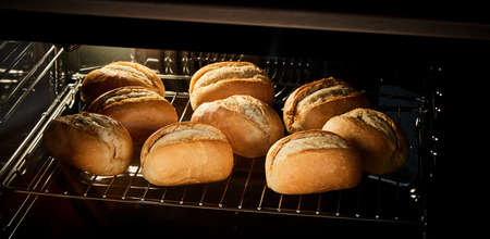 Bunch of fresh crispy buns placed on grate inside hot oven in kitchen