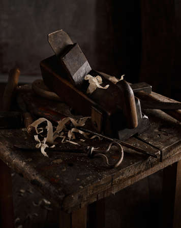 High angle of various aged carpentry instruments placed on shabby lumber table in dark joinery Stockfoto