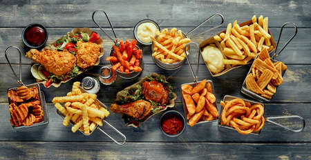 High angle of different types of French fries placed near roast chicken served with lettuce leaves and sauces on table