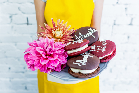 womens hands: Whoopie pies on a tray with flowers, womens hands. Congratulations.