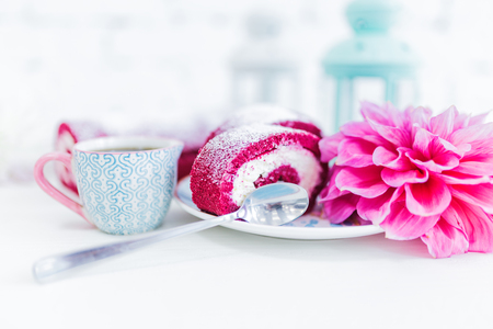 A red velvet cake roll sliced with cup of coffee or tea and flowers. Stock Photo