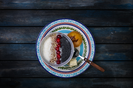 Sweet rice porridge with berries nuts and coconut chips, top view. Healthy breakfast or dessert. Bread with butter. Top view Stock Photo