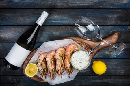 Large shrimp or langoustine with white sauce, bottle of wine, glass for the wine and half of a lemon on a wooden board. Top view 版權商用圖片