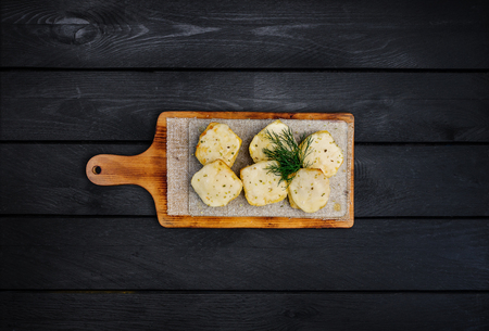 Bread with cheese. Fried garlic croutons with dill. On a wooden board. Top view. Black wooden background Zdjęcie Seryjne