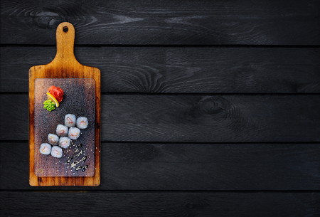 Classic sushi roll with shrimp on a wooden board. Top view. Black wooden background