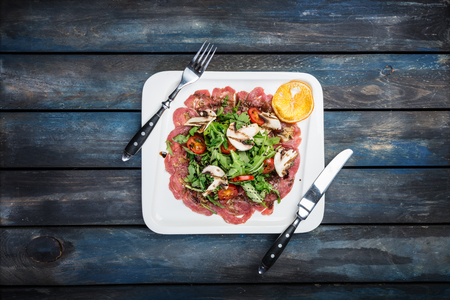Beef carpaccio with mushrooms on wooden background with cutlery